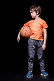 Serious boy holding basketball ball and looking away Royalty Free Stock Image