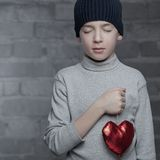 Serious boy holding heart, studio Royalty Free Stock Photos