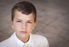 Serious boy looking at camera. Portrait of boy dressed in suit. Shallow depth of field, slight vignette Stock Photography