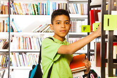Serious boy looks and searches book on shelf. Serious boy looks straight and searches book on shelf in library Stock Photography