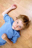 Serious boy lying on the floor Royalty Free Stock Photography