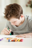 Serious Boy Making Art on Paper Using Crayons Stock Image