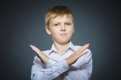 Serious boy making X sign with him arms to stop doing something.  Royalty Free Stock Photo