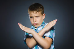 Serious boy making X sign with him arms to stop doing something.  Royalty Free Stock Photography