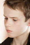 Serious boy with messy brown hair frowns. Head shot of serious boy with messy brown hair and wearing a black shirt frowns away from the camera stock image