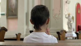 Serious boy praying in the Church alone stock photography