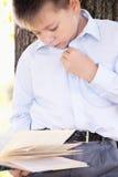 Serious boy reading book Stock Image