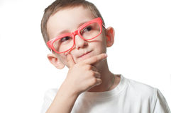 Serious boy in red glasses thinks. Serious boy in red glasses isolated on the white background Stock Photo