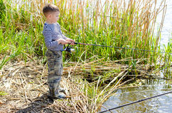 Serious Boy at the Riverside Holding Fishing Rod Stock Photography
