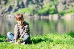 Serious boy sits on the green bank of a big river. On a sunny morning and looks at the camera Stock Image