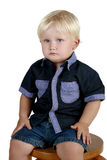 Serious boy sits on a stool Royalty Free Stock Images