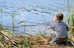 Serious Boy Sitting on Riverside While Fishing Stock Photos