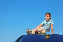 Serious boy sitting on roof of car Stock Photo