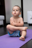 Serious boy sitting on a yoga Mat Stock Photography