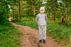 A serious boy of six years in the gray hat and the hoodie is in green summer forest. The boy in full length stock photography