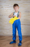 Serious boy in slippers putting on gloves Royalty Free Stock Images