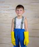 Serious boy in slippers putting on gloves Royalty Free Stock Image