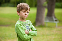 Serious boy standing with arms crossed at park Stock Photo