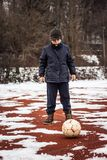Serious boy standing in front of ball Royalty Free Stock Photo
