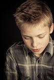 Serious boy in striped shirt looking downward. Serious blond boy in striped shirt over black background looking downward for concept about loneliness or Royalty Free Stock Photos