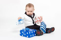 Serious boy in suit arranging presents Royalty Free Stock Photos