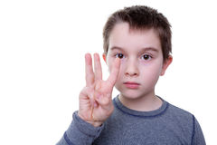 Serious boy with three fingers up. Close up of serious little boy gesturing with three fingers as if to count or display a symbol Royalty Free Stock Image