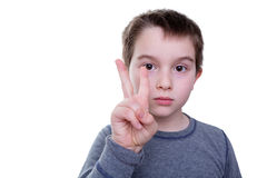 Serious boy with two fingers up stock photos