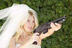 Serious bride. Beautiful bride holding a shotgun Stock Photography