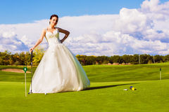 Serious bride playing golf on field Royalty Free Stock Photography