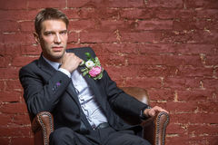 Serious bridegroom looking and sits. In a leather chair against a brick wall stock images