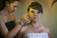 Serious bridesmaid helps young bride with earrings. Young sad bride getting help with earrings Royalty Free Stock Photo