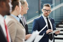 Contemporary broker. Serious broker in suit and eyeglasses looking at his colleagues during training at business briefing while presenting and explaining them royalty free stock images