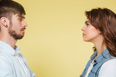 Serious brother and sister looking at each other. Serious brother and sister dressed casual looking at each other isolated over yellow Royalty Free Stock Photography