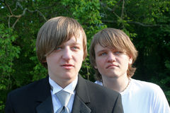 Serious Brothers In Tux And T-Shirt. Closeup of two serious brothers with serious expressions, one dressed in a tux and looking at the viewer, the other dressed Stock Images