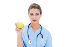 Serious brown haired nurse in blue scrubs holding a green apple Royalty Free Stock Photos