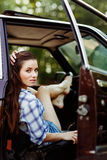 Serious brunette in burgundy car , tinted photo. Serious brunette in burgundy car in short shorts, tinted photo Royalty Free Stock Photography