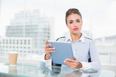 Serious brunette businesswoman holding tablet Royalty Free Stock Photo
