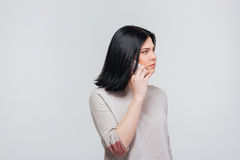 Serious brunette girl making a phone call. Serious pretty brunette girl making a phone call isolated on a white background Royalty Free Stock Image