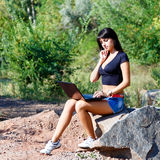 Serious brunette girl using laptop sitting on a stone Stock Images