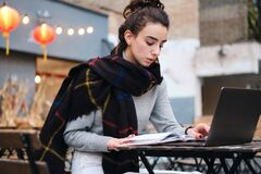 Free Serious Brunette Girl With Scarf Thoughtfully Reading Book Studying With Laptop In Cafe On City Street Royalty Free Stock Photos - 184611208