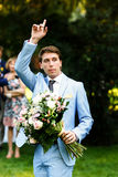 Serious brunette groom in blue dress with a bouquet of flowers r Stock Photos