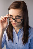 Serious brunette holding glasses posing Royalty Free Stock Photo