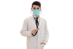 Serious brunette male doctor in uniform with stethoscope on his neck and mask posing and looking at the camera isolated Royalty Free Stock Image