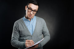 Serious brunette male person making some notes. Repeat please. Self-confident male wearing smart clothes holding opened notebook in left hand while looking Royalty Free Stock Photo