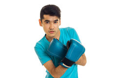 Serious brunette sports man oracticing boxing in blue gloves isolated on white background Stock Photos