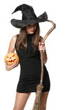 The  serious  brunette witch with a broom Stock Images