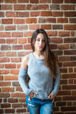Serious brunette woman against red brick wall closeup photo Stock Images
