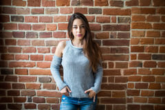 Serious brunette woman against red brick wall closeup photo Royalty Free Stock Photography