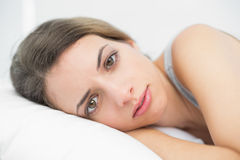 Serious brunette woman lying on her bed in the bedroom Royalty Free Stock Photo