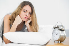 Serious brunette woman lying on her bed under the cover Royalty Free Stock Image